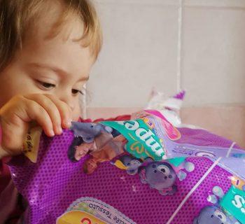 bambina apre confezione di pannolini Pampers